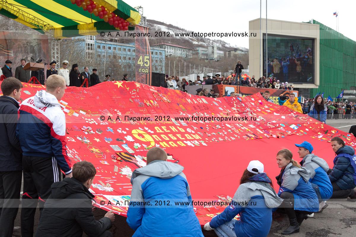 Фотография: День Победы. Знамя Победы, которое жители полуострова Камчатка изготовили своими руками из десятков художественно оформленных отрезков красной ткани. Размер полотнища — 15 на 15 метров