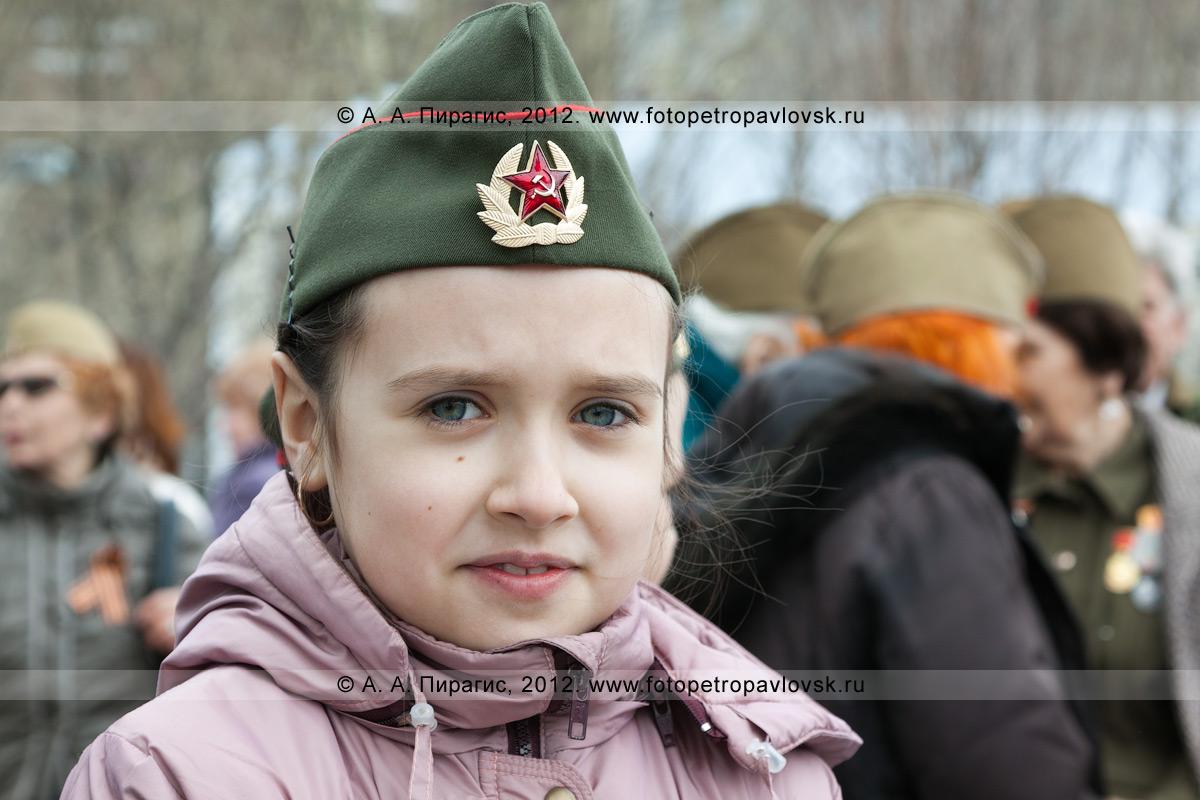 Фотография: девочка в солдатской пилотке — участница праздничного концерта в День Победы на площади Ленина в городе Петропавловске-Камчатском