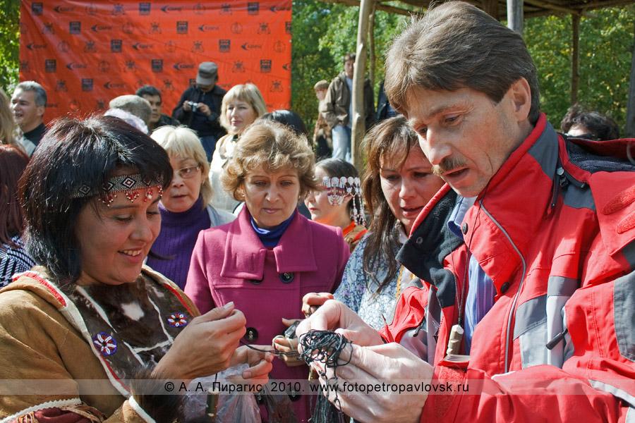 Фотография: прошедшим ительменский обряд очищения вешают на шею хантайчик — фигурку в виде человека-рыбы, который будет оберегать от бед и приносить удачу в рыбной ловле. Справа на фотографии — Виктор Махиня — министр общественных отношений Камчатского края
