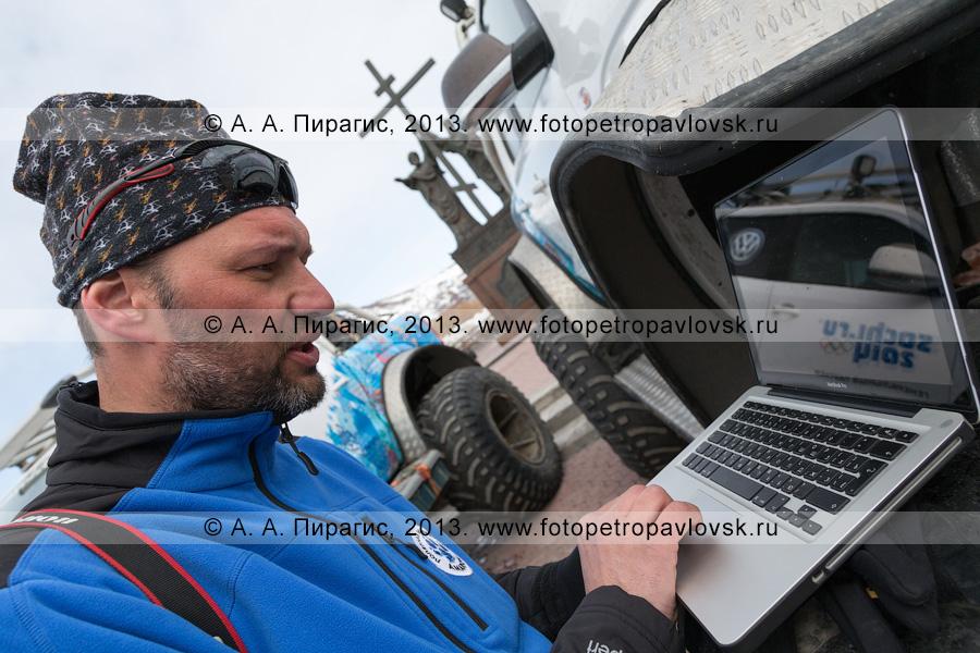 """Фотография: участник полярной автомобильной экспедиции """"Амарок. Путь северного волка"""" работает на ноутбуке, расположенном на колесе автомобиля Volkswagen Amarok"""