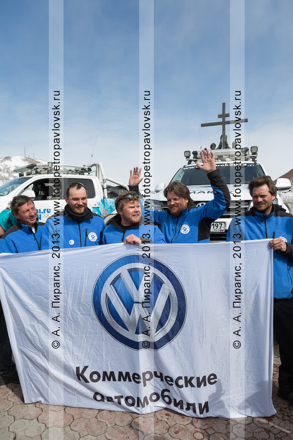 """Фотография: участники полярной автомобильной экспедиции """"Амарок. Путь северного волка"""" с флагом спонсора — производителя автомобилей Volkswagen"""