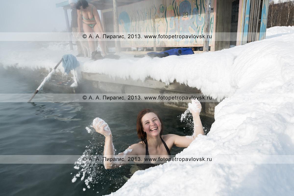 Фотография: радостная девушка обтирается снегом в бассейне с природной горячей водой в селе Анавгай на Камчатке