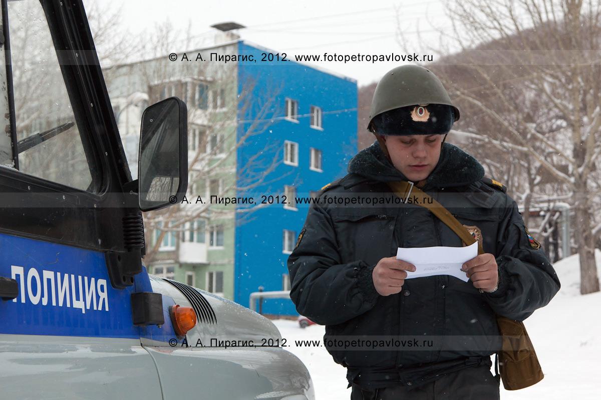 Фотография: полицейский читает требования террористов, которые захватили здание избирательного участка с людьми. Антитеррористические учения по пресечению теракта на объекте массового пребывания людей. Камчатский край, город Петропавловск-Камчатский