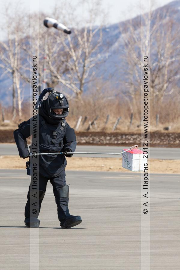Фотография: специалист-подрывник (сапер) с помощью манипулятора несет взрывное устройство (бомбу) к месту ее уничтожения. Контртеррористические учения по пресечению теракта на объекте воздушного транспорта