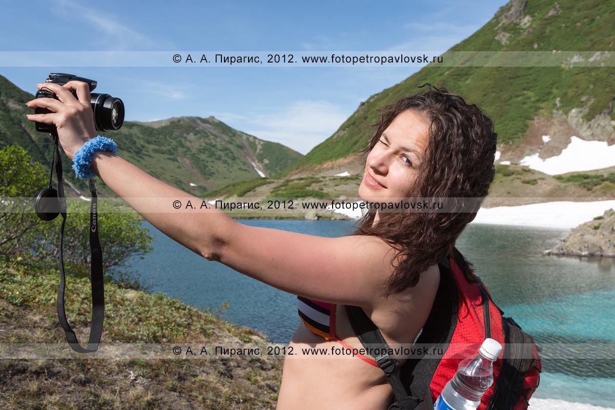 Фотография: девушка-туристка фотографируется на Голубых озерах на полуострове Камчатка