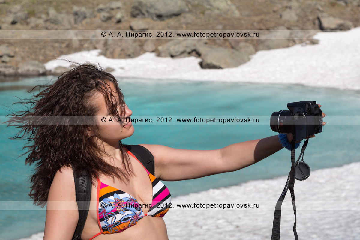 Фотография: девушка-туристка фотографируется (делает селфи) на фоне Голубых озер на полуострове Камчатка