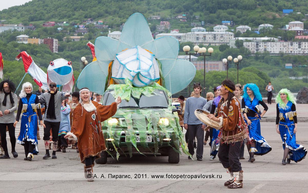 Фотография: украшенный автомобиль везет Нептуна с супругой Салацией в сопровождении свиты. На переднем плане — участники театрализованного шествия в национальных костюмах коренных жителей Камчатки. День рыбака в Петропавловске-Камчатском