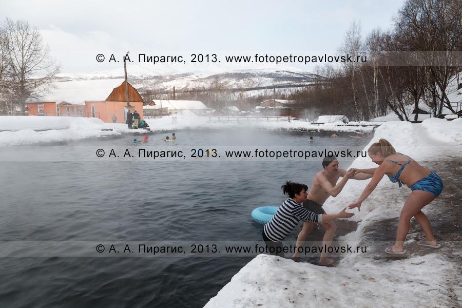 Фотография: туристы входят в бассейн с термальной водой, который расположен в центре села Эссо на полуострове Камчатка