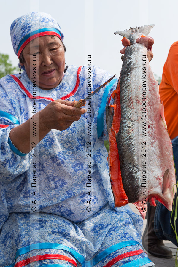 Фотография: женщина разделывает красную рыбу. Конкурс по разделке красной рыбы в День первой рыбы