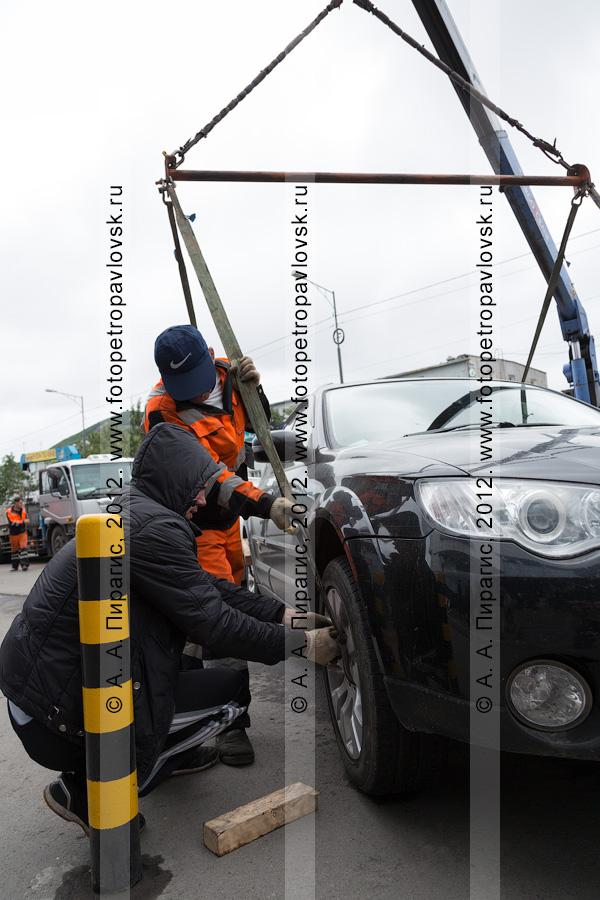 Фотография: рабочие прикрепляют стропы к колесам автомобиля для его дальнейшего подъема на эвакуатор