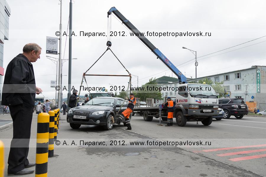 Фотография: рабочие подготавливают автомобиль для погрузки на эвакуатор
