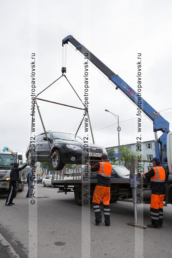 Фотография: погрузка автомобиля на эвакуатор для дальнейшей транспортировки на специальную стоянку