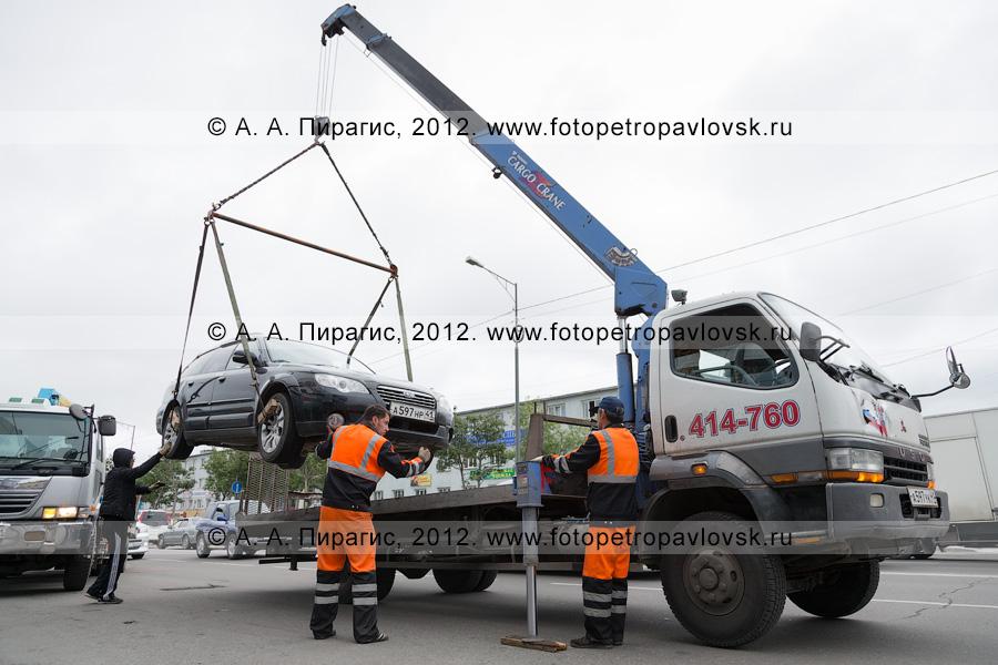 Фотография: погрузка автомобиля краном-манипулятором на эвакуатор для дальнейшей транспортировки на специальную стоянку