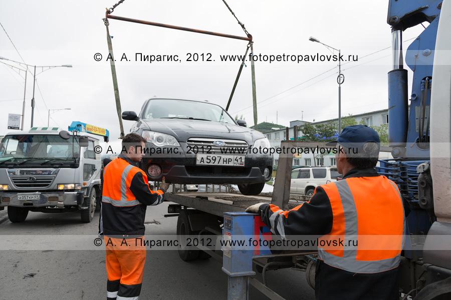 Фотография: рабочие грузят автомобиль на эвакуатор для его транспортировки на спецстоянку