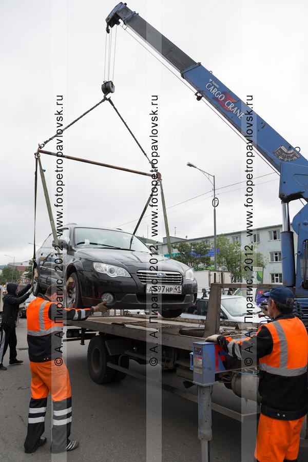 Фотография: погрузка транспортного средства на эвакуатор с помощью крано-манипуляторной установки