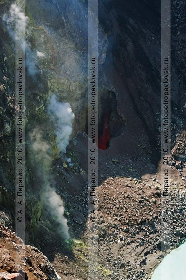 Фотография: бокка (отверстие) в стенке активного кратера вулкана Горелого. Бокка находится на берегу кислотного озера. Из отверстия под давлением выходит раскаленный газ