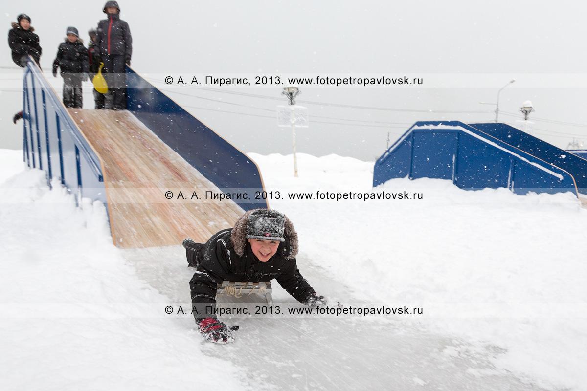 Фотография: мальчик на санках съезжает с ледяной горки. Петропавловск-Камчатский