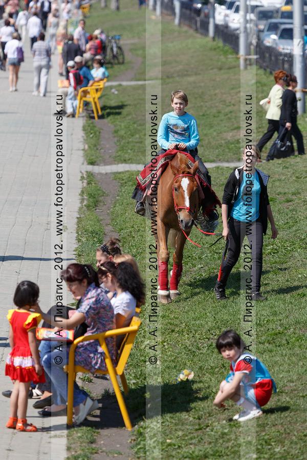 Фотография: катание на лошади по газону на Озерновской косе в городе Петропавловске-Камчатском
