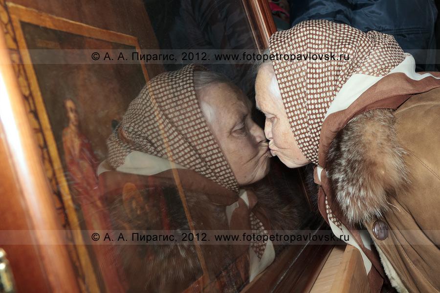 """Фотография: прихожанка целует икону """"Спас Смоленский"""". Кафедральный собор Святой Живоначальной Троицы. Камчатский край, город Петропавловск-Камчатский"""