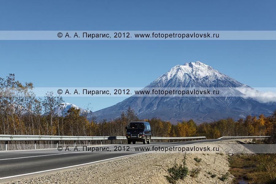 Фотография: микроавтобус едет по дороге на фоне Корякского вулкана (Корякская сопка) на Камчатке