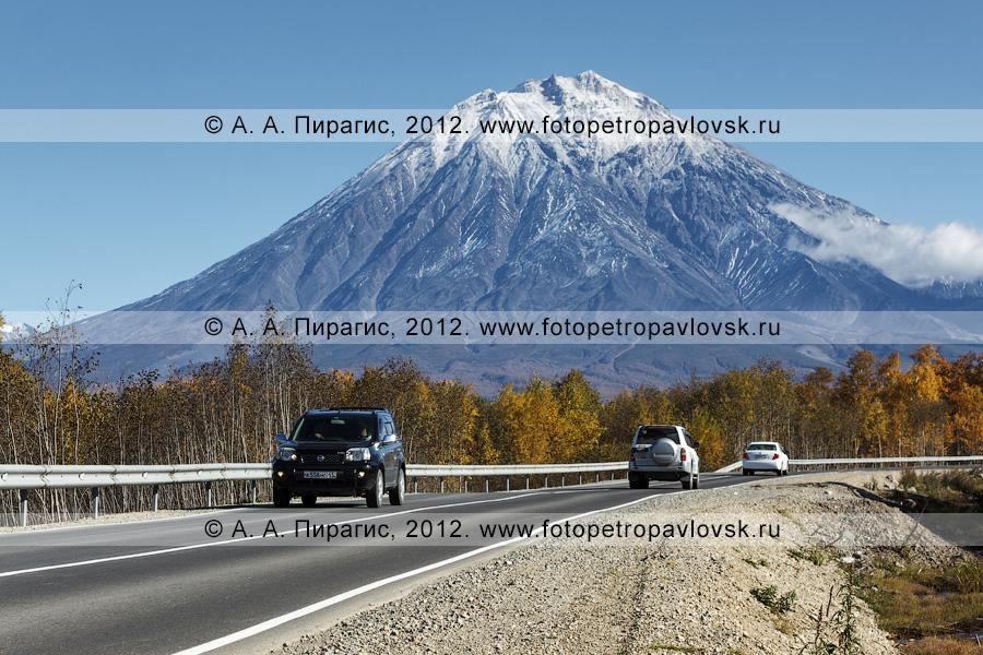 Фотография: движение автотранспорта по дороге на фоне Корякского вулкана на полуострове Камчатка