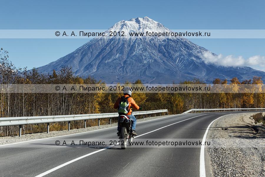 Фотография: мотоцикл едет по дороге на фоне Корякского вулкана (Корякская сопка). Камчатский край, Елизовский район