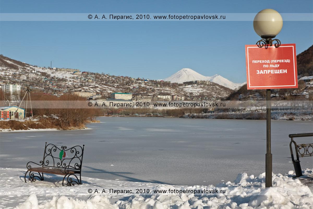"""Фотография: замерзшее Култучное озеро в центре Петропавловска-Камчатского. Надпись на плакате: """"Переход (переезд) по льду запрещен"""""""