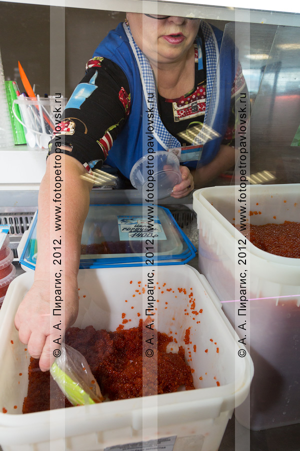 """Фотография: продавец накладывает икру лососевую зернистую в банку. Отдел """"Рыба и морепродукты"""" ОАО ОБ """"Камчатпромтовары"""""""