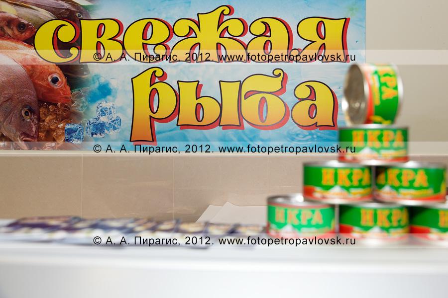 """Фотография: плакат """"Свежая рыба"""" на фоне банок с красной икрой"""