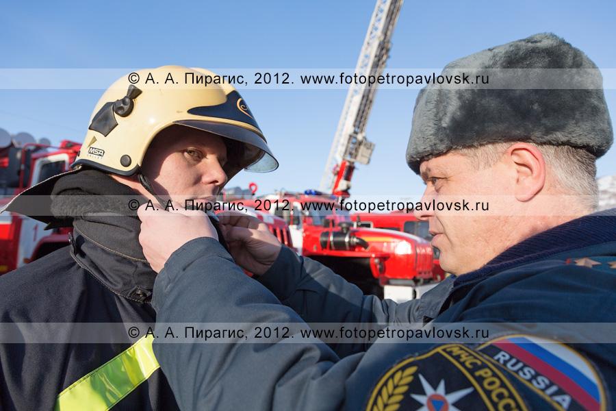 Фотография: подполковник Кухтинов Василий по-отечески помогает пожарному застегнуть ремешок на каске