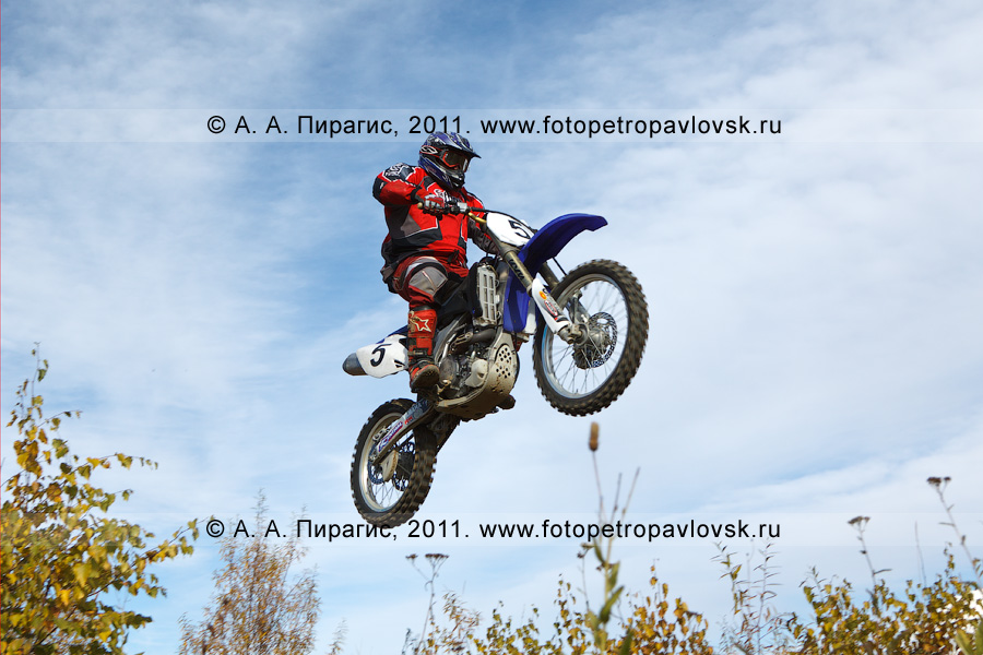 Фотография: камчатский спортсмен-мотоциклист летит над трассой. Мотокросс в городе Елизово на Камчатке