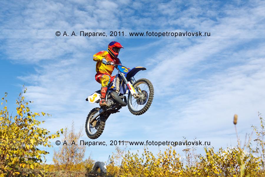 Фотография: камчатский спортсмен-мотогонщик летит с трамплина. Спортивные состязания по мотокроссу в городе Елизово на Камчатке