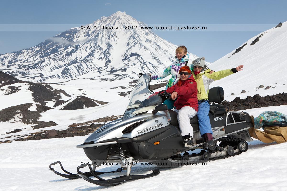 Фотография: девушки позируют на снегоходе. Авачинский перевал, Камчатка. На заднем плане: Корякский вулкан