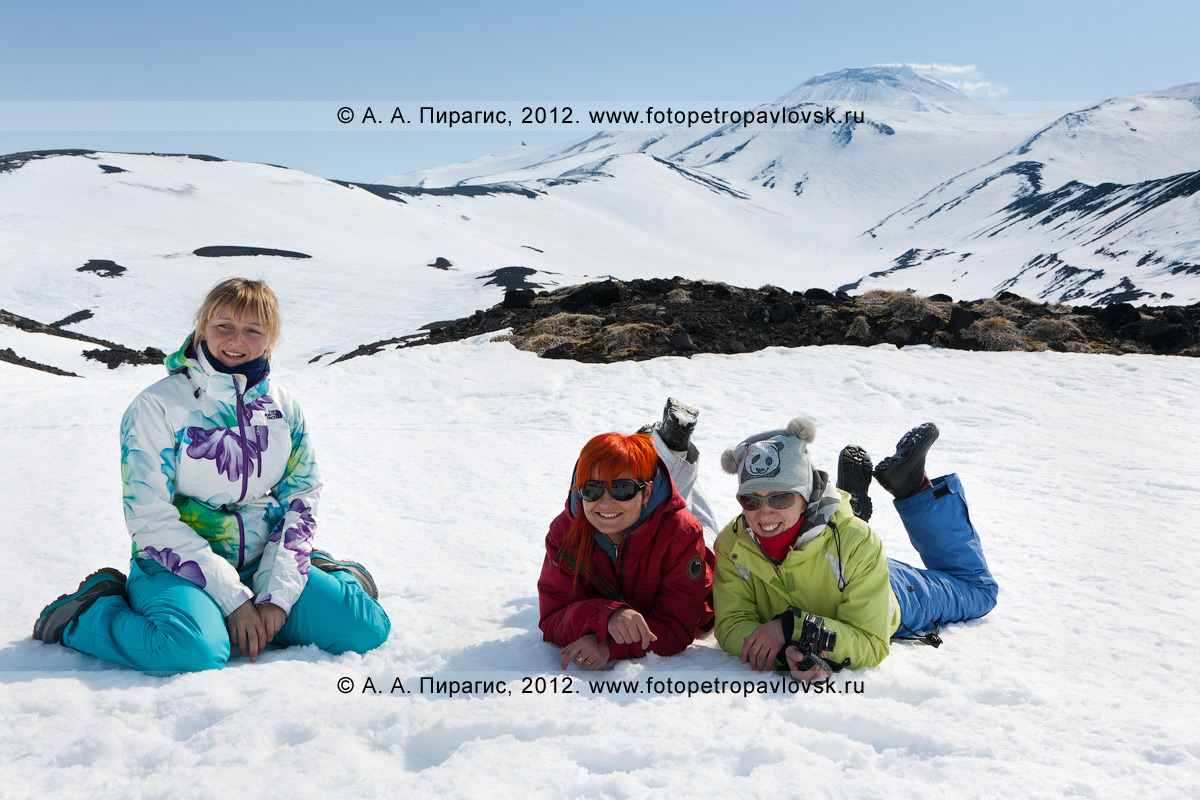 Фотография: девушки на снегу. На заднем плане: Авачинский вулкан на Камчатке
