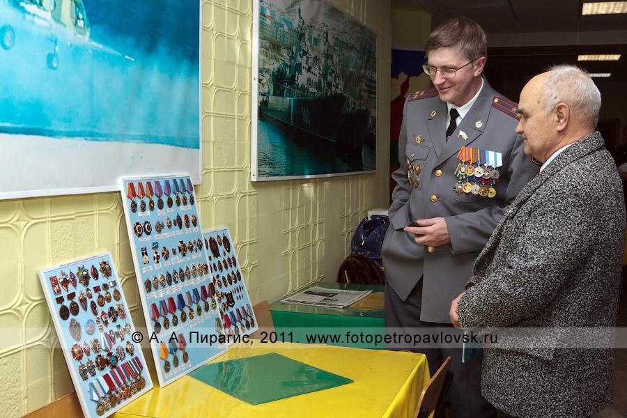 Фотография: Давыдов Александр (слева) показывает коллекцию медалей, знаков и значков органов внутренних дел России