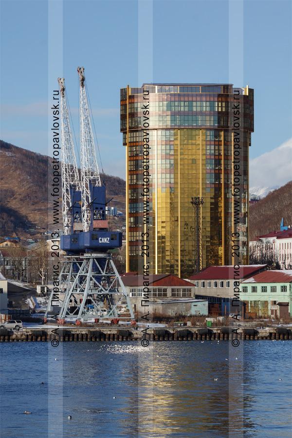Фотография: портовые краны в петропавловском порту и высотное офисно-административное здание в центре города Петропавловска-Камчатского. Камчатский край