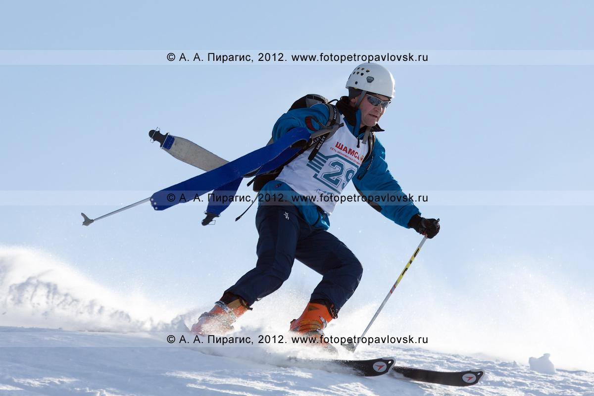 Фотография: участник соревнований по ски-альпинизму едет с горы, держа в руках камус. Соревнования по ски-альпинизму. Полуостров Камчатка, Петропавловск-Камчатский