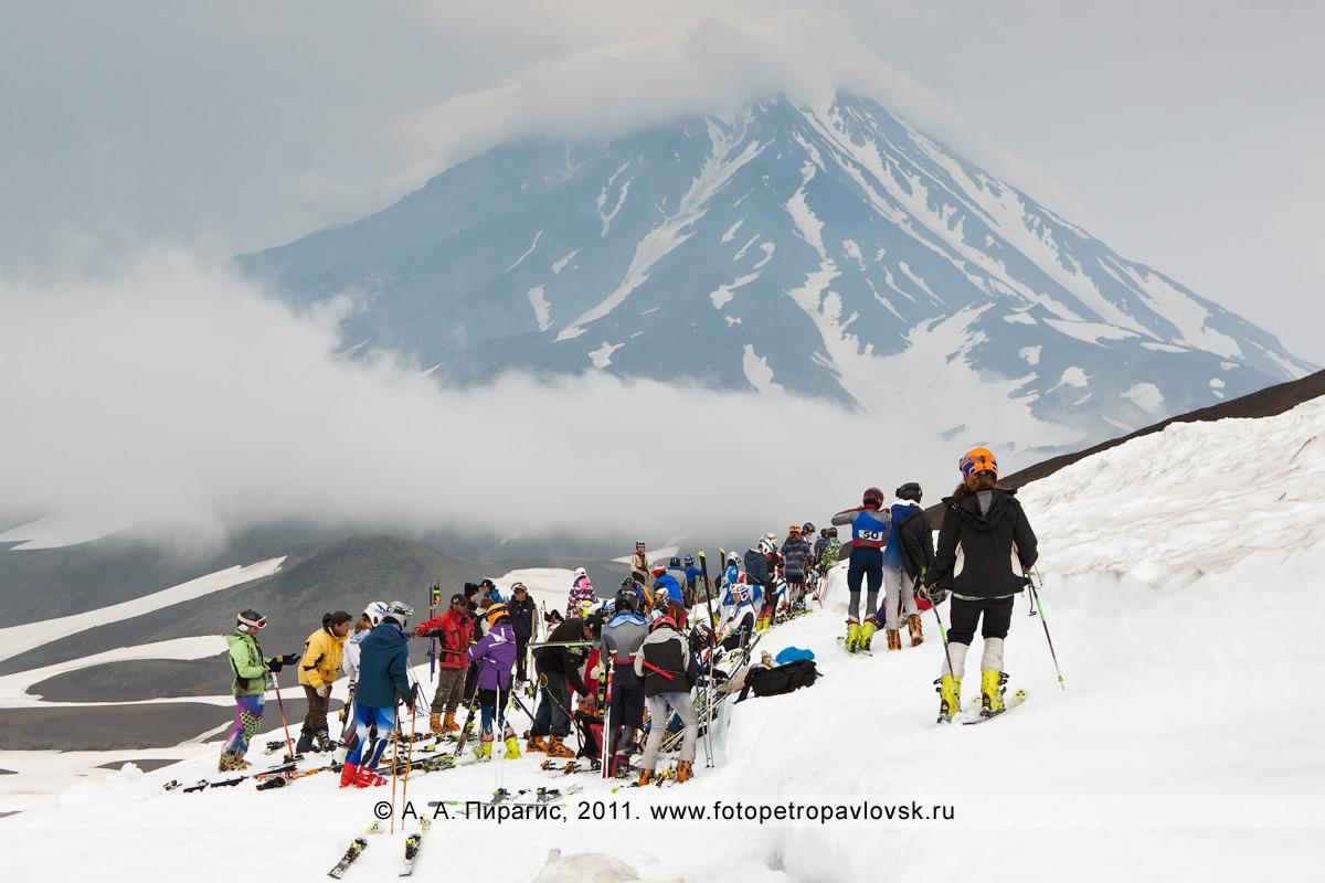 Фотография: участники соревнований по горнолыжному спорту на месте старта. На заднем плане — Корякский вулкан
