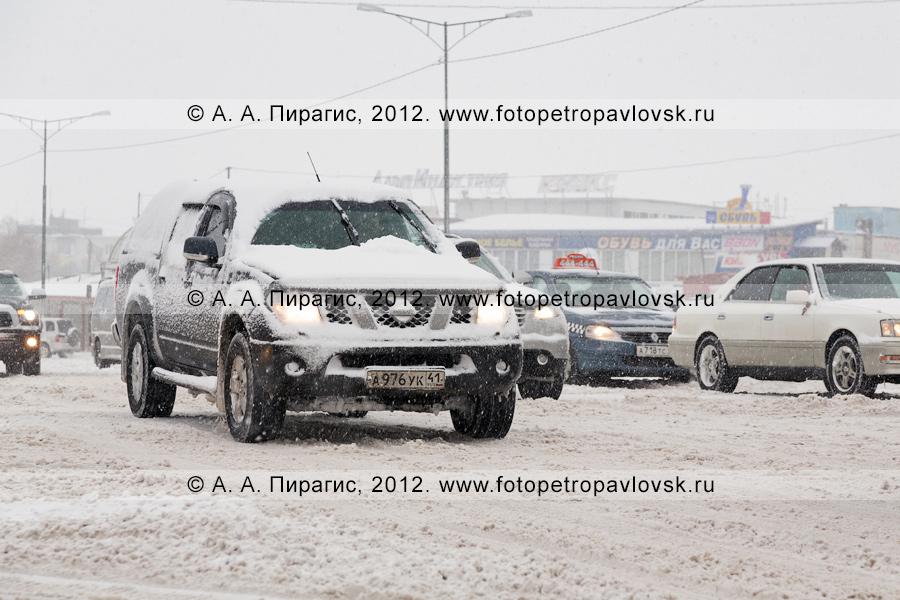 Фотография: снегопад в городе Петропавловске-Камчатском. Движение заснеженного автотранспорта по дороге