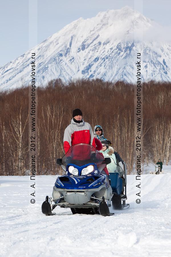 Фотография: путешествие на снегоходе по лесу. На заденем плане: Корякский вулкан — действующий вулкан на полуострове Камчатка