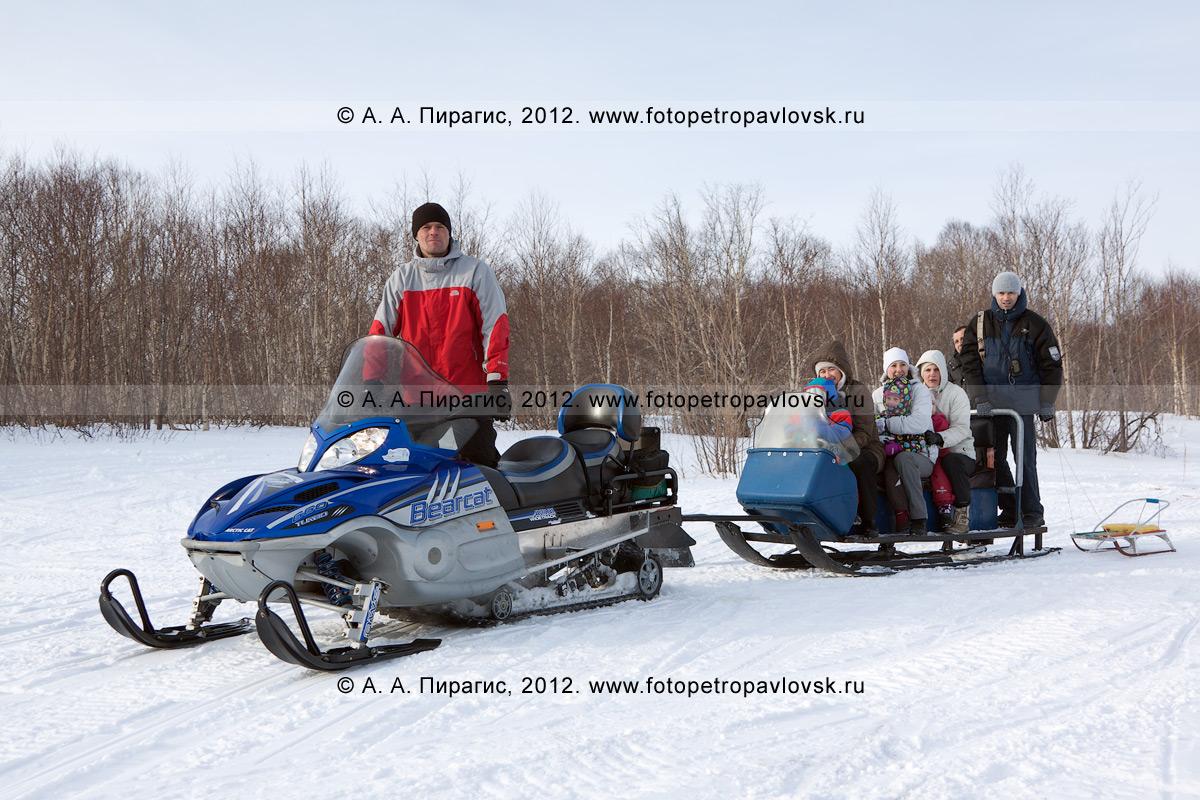 Фотография: снегоход буксирует нарты с туристами по зимнему лесу. Камчатский край, окрестности города Петропавловска-Камчатского