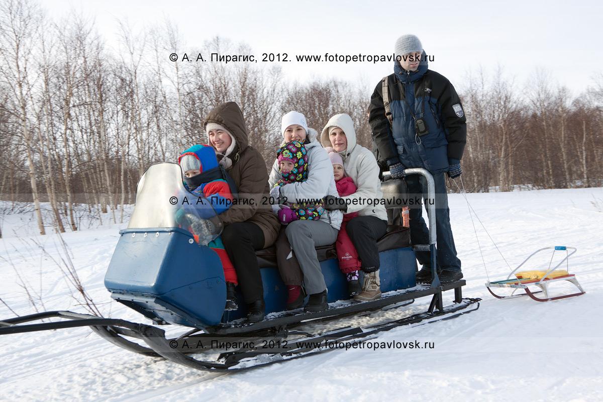Фотография: нарты с камчатскими туристами, которые тянет снегоход. Полуостров Камчатка, окрестности города Петропавловска-Камчатского