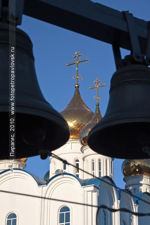 Фотография: колокола звонницы на фоне куполов собора Святой Живоначальной Троицы в городе Петропавловске-Камчатском