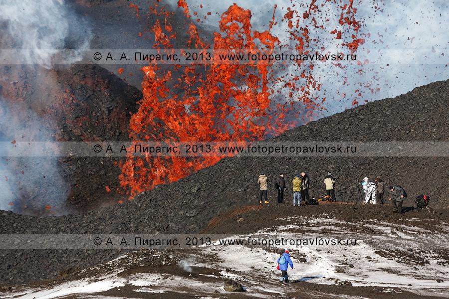 Фотография: туристы на фоне фонтанирующей из кратера лавы прорыва имени вулканолога Софьи Набоко. Извержение вулкана Плоский Толбачик на Камчатке