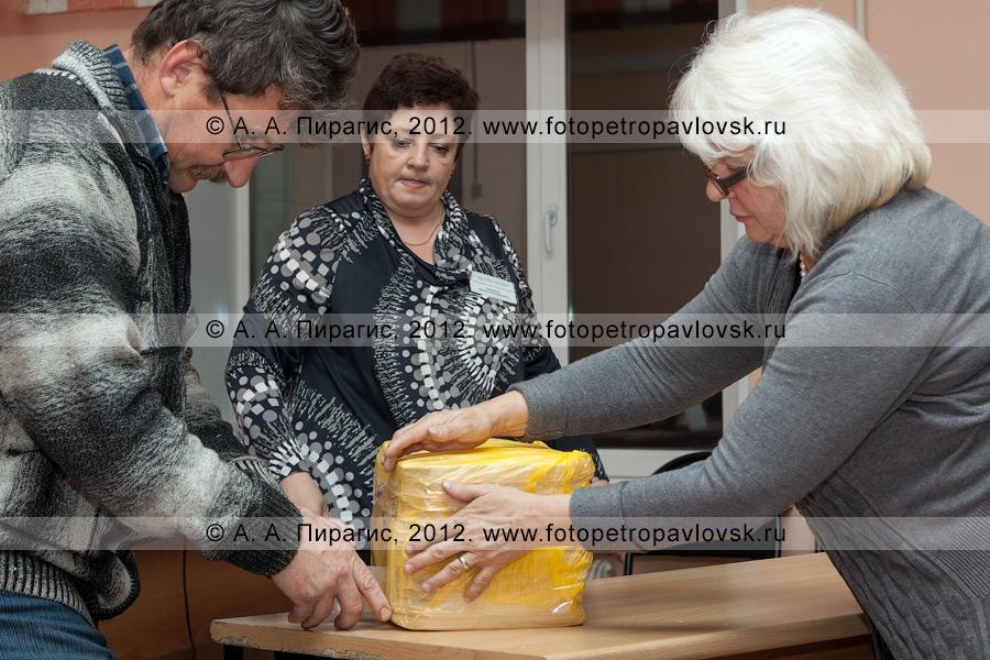 Фотография: процедура упаковывания гашеных избирательных бюллетеней для голосования