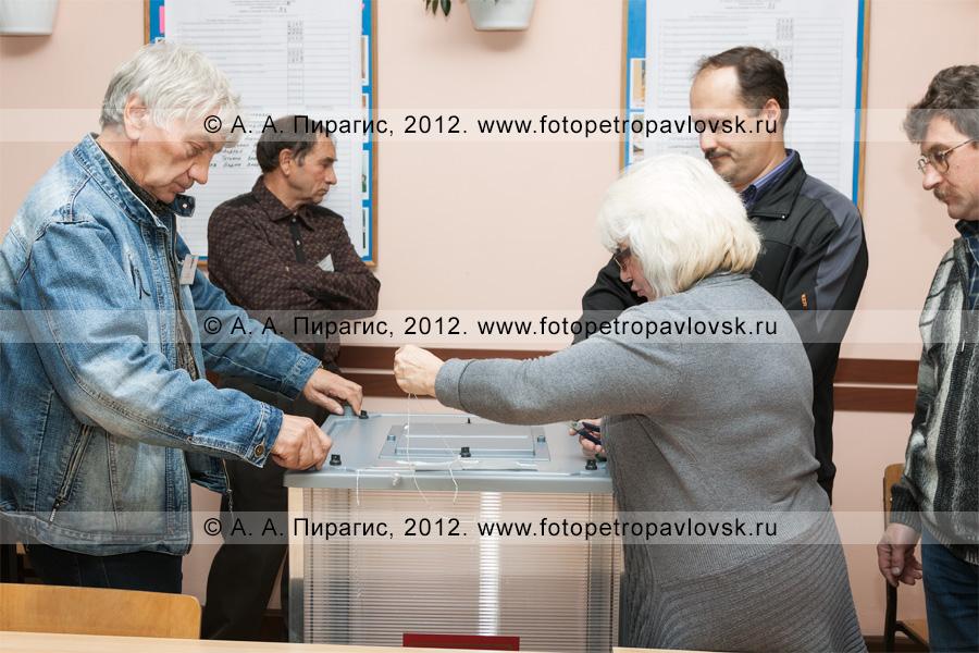 Фотография: сотрудники участковой избирательной комиссии избирательного участка № 51 вскрывают стационарную урну для голосования на выборах