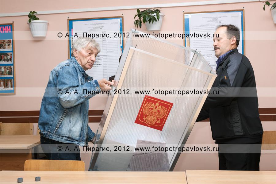 Фотография: члены участковой избирательной комиссии избирательного участка № 51 переворачивают стационарную урну для голосования на выборах, чтобы достать из нее избирательные бюллетени для их дальнейшего подсчета