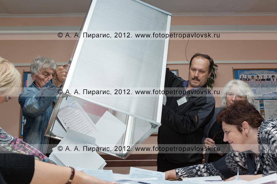 Фотография: сотрудники участковой избирательной комиссии избирательного участка № 51 достают избирательные бюллетени из стационарной урны для голосования на выборах