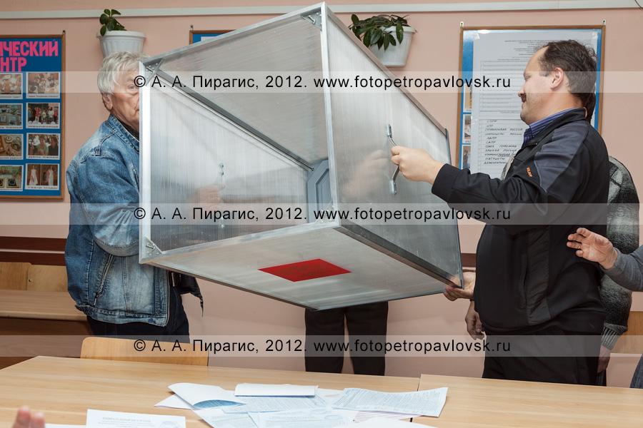 Фотография: члены участковой избирательной комиссии избирательного участка № 51 демонстрируют наблюдателям на выборах пустую стационарную урну для голосования после извлечения из нее избирательных бюллетеней