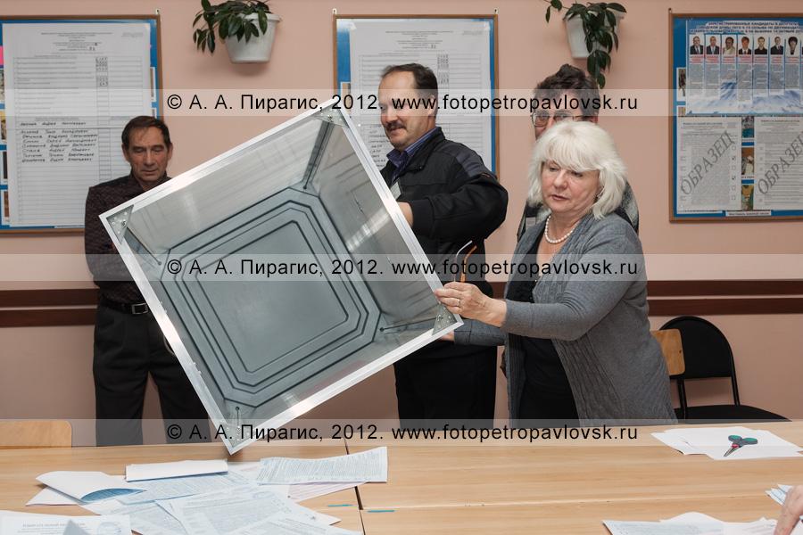 Фотография: сотрудники участковой избирательной комиссии избирательного участка № 51 показывают наблюдателям на выборах опустошенную стационарную урну для голосования после изъятия из нее избирательных бюллетеней